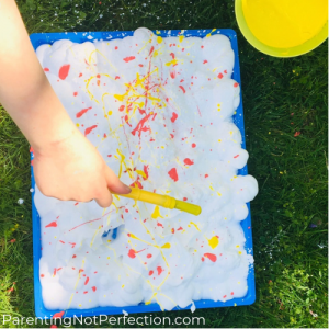 Paint Splattered Shaving Cream with hand holding paintbrush splattering paint