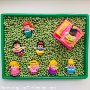 Little people princesses laying in a tray of frozen peas