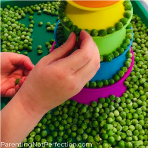 hand placing peas on rainbow toy
