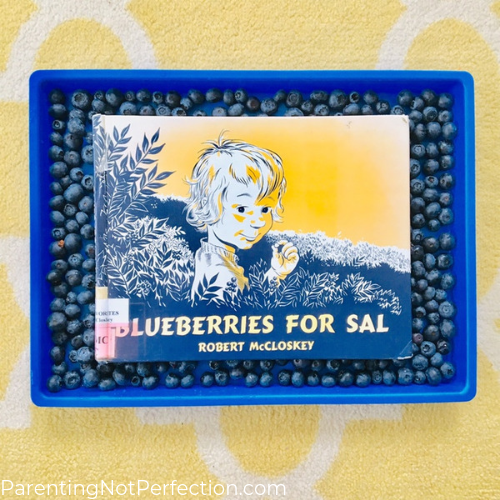 Blueberries for sal book laying on top of blueberries in a tray. Blueberry water play