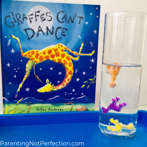 "3 colorful giraffes floating at different levels in a tall glass with clear liquid with ""Giraffes Can't Dance"" book next to it"