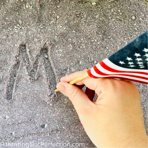 hand holding American flag writing the letter M in moon sand