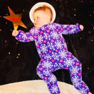 baby astronaut on moon holding a gold star