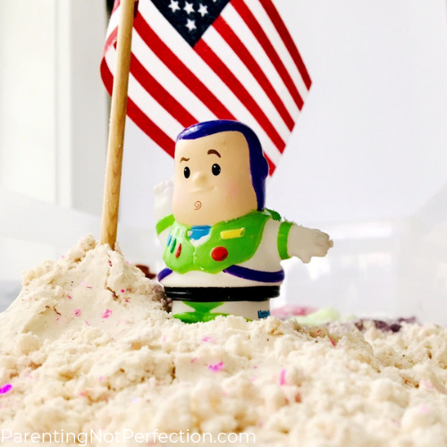 Little People Buzz Lightyear standing in moon sand next to American flag