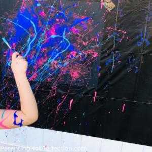 hand holding paintbrush splattering blue paint on black poster board