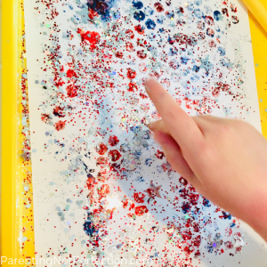 hand adding glitter to bubble wrap painted flag art.