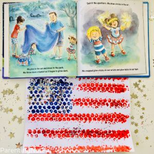 """The Night Before the Fourth of July"" open to a page showing parents putting a picnic blanket out and kids playing with sparklers. Our bubble wrap painted flag art."