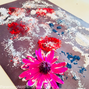 black paper with red, white, and blue paint on it and a bright pink flower sitting on top with some white paint on the petals. making flower painted fireworks.