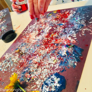 hand sprinkling glitter on a messy red, white, and blue painted paper. making flower painted fireworks.