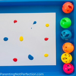 white paper with red, yellow and blue paint splots on it with 6 colorful cat toy balls lined up next to it.