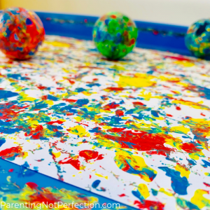 close up of cat toy balls rolling in paint on white paper