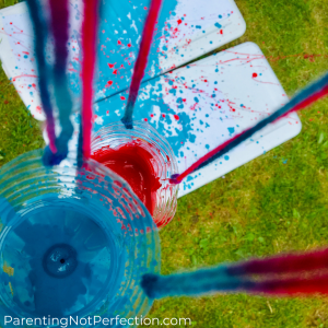 a birds eye view from above the pendulum painting water bottles with red and blue paint in them and the red and blue painting underneath