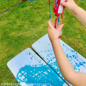 hands squeezing red paint in to water bottle pendulum with blue painted paper underneath in the grass