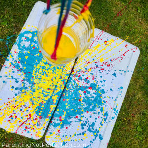 a birds eye view from above the pendulum painting water bottle with yellow paint in it and the red, blue & yellow painting underneath