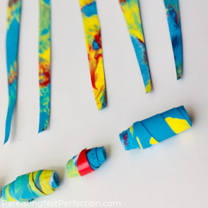 close up of paper beads and triangular strips of pendulum painted rainbow paintings.