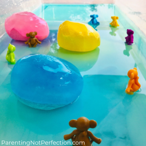 Colorful monkeys in pool of colorful water with 3 frozen goop balls pink, yellow & blue.