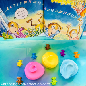 "Colorful monkeys in pool of colorful water with 3 frozen goop balls pink, yellow & blue with ""Five Little Monkeys Play Hide-and-Seek"" open next to it."