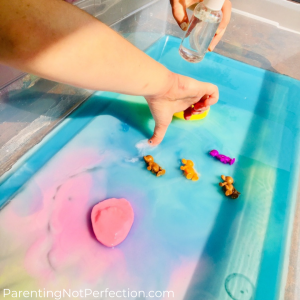 hand drawing a design by scrapping the goop hidden under the colorful water.