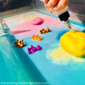 hand squeezing water bottle at yellow frozen goop ball, with colorful monkeys laying in pool of colorful water next to it.