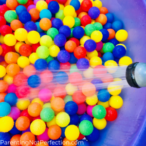 Water coming out of hose spraying balls in pool to make an outdoor ball pit.