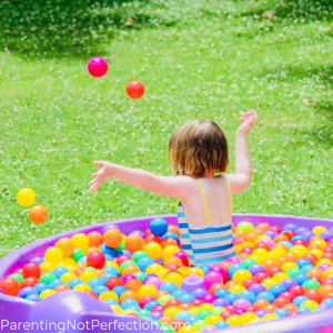 Child playing in pool of water and balls ball pit throwing some in the air.