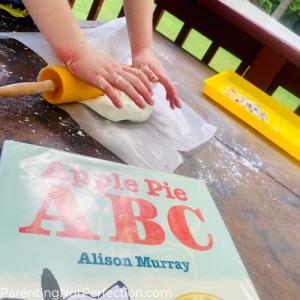 hands using rolling pin to flatten apple pie dough