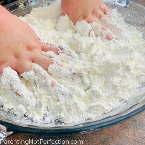 messy hands mixing hair conditioner and cornstarch to make apple pie dough