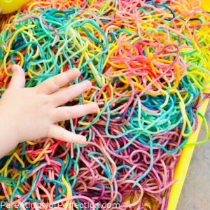 a baby hand touching colored spaghetti