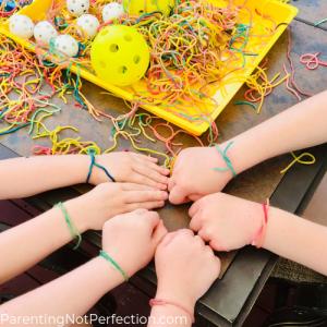 six hands showing colored spaghetti friendship bracelets on each wrist