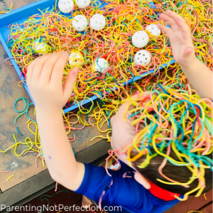 a boy with colored spaghetti on his head and a mess of pasta and wiffle balls all over the table