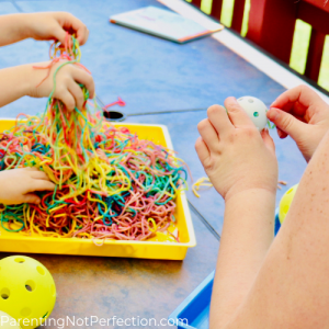 hands playing with colored papta and other hands threading spaghetti through wiffle balls