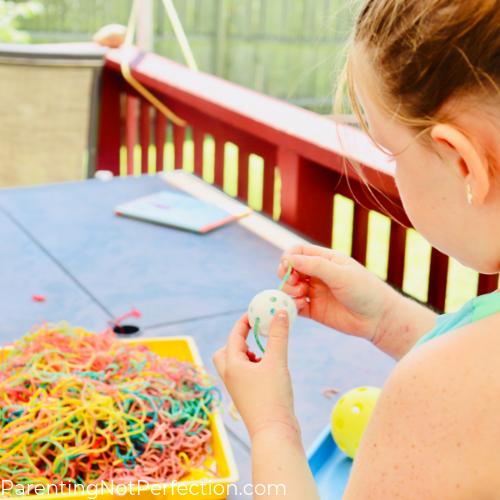 a girl threading colored spaghetti through a wiffle ball