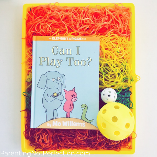 """Can I Play Too?"" book on a tray of colored spaghetti with wiffle balls"