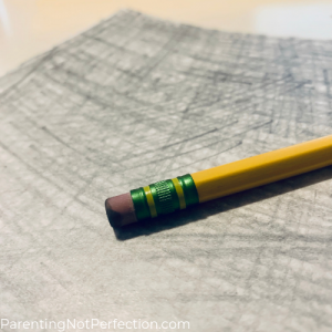 a pencil with an eraser sitting on top of a shaded in paper