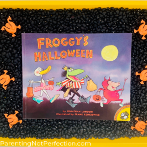 """Froggy's Halloween"" book on bed of black beans with orange flip frogs"