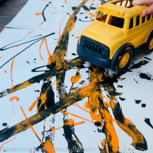 school bus toy wheeled through orange and black paint