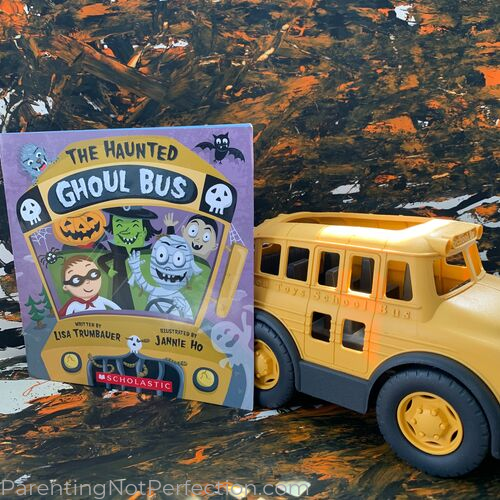 The Haunted Ghoul Bus book next to a toy school bus and orange and black painting