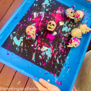 skulls rolling around in paint on a tray