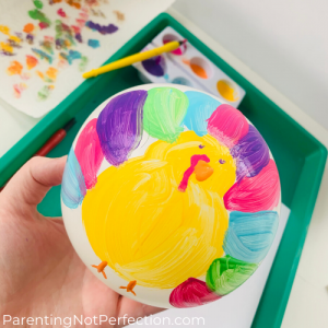 hand holding painted turkey balloon before printing it onto paper