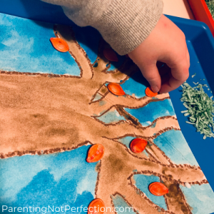 hand placing red colored pumpkin seed on tree painting