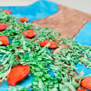 "close up of pumpkin seed ""apples"" and green colored coconut flake ""leaves"" on painted tree"