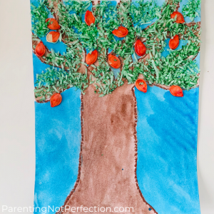 completed apple tree painting with green coconut flake leaves and red pumpkin seed apples.