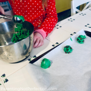 a child scooping cookie dough out of a bowl onto a cookie sheet.