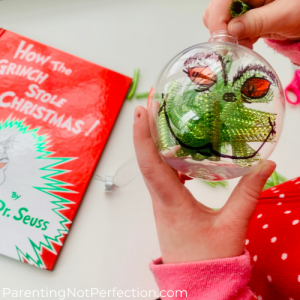 child holding clear globe ornament placing pieces of green mesh tube inside.