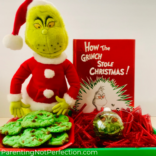 the grinch doll sitting holding a plate of grinch cookies next to how the grinch stole christmas book with a homemade ornament