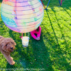 hot air balloon glitter sprinkler on zipline headed toward girl laying in grass with dog next to her