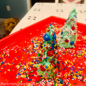 edible trees on a tray with sprinkles and a dog looking at them in the background