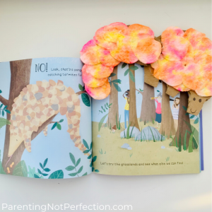 we're off to find a unicorn book opened to page showing pangolin on a tree branch with our peek-a-boo pangolin art