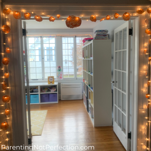 lit up celery print marigold garland hanging in doorway of homeschool room