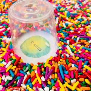 "clear plastic shot glass finding hidden letter ""I"" in a tray full of sprinkles"